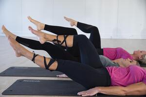 Tre jenter som som ligger på rygg og gjør øvelser for magen